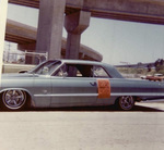 Brown Image Car Club: Photograph of a 1963 Chevrolet Impala displaying a poster promoting an upcoming dance