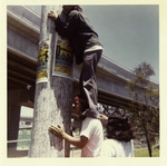 Brown Image Car Club: Photograph of club member Henry Rodriguez hanging up a poster for a club event