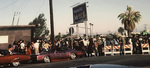 Brown Image Car Club: Photograph of a block party outside the clubhouse, featuring a 1967 Buick Rivera belonging to Oscar Eribez