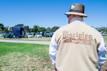 Disciples Car Club: Photograph of Disciples Car Club member wearing club jacket at Lowrider Council event at Mission Bay