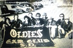 Oldies Car Club: Photograph of car club members with banner